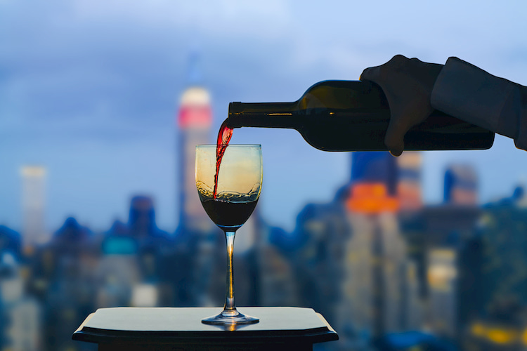 Pouring a glass of wine in front of the New York City skyline
