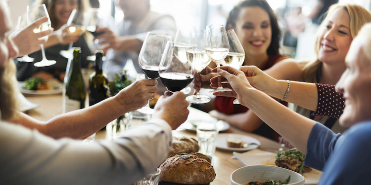 Group enjoy dinner and toasting with wine