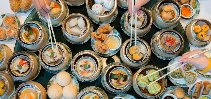 overhead view of a restaurant table full of dim sum plates