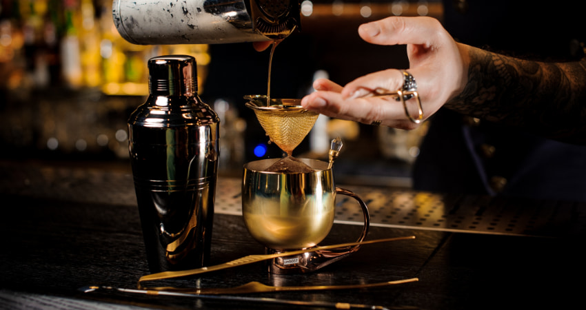 bartender pours a Progibition-style cocktail at a New York City speakeasy