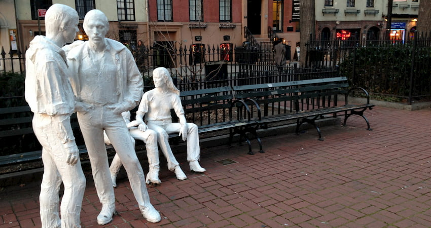 the Gay Liberation art installation in Christopher Park in New York City, with Stonewall Inn in the background