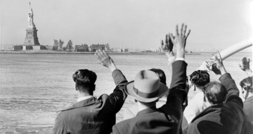 old photo of immigrants waving at the Statue of Liberty from a boat