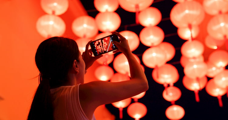a woman takes a photo of red lanterns at a lunar new year festival