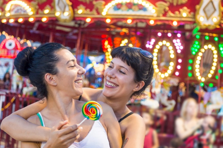 Two girls embracing each other in front of a colorful carousel