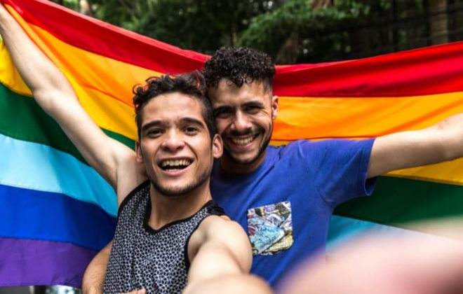 a gay couple holding a pride flag and smiling