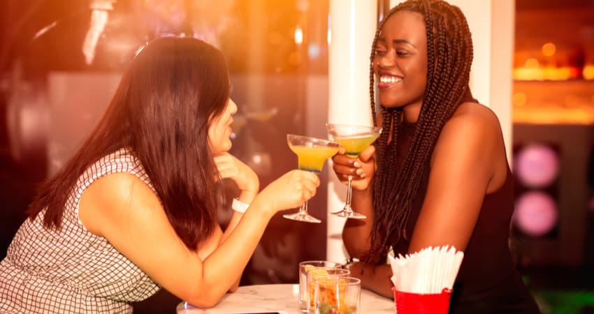 two women drinking at a bar