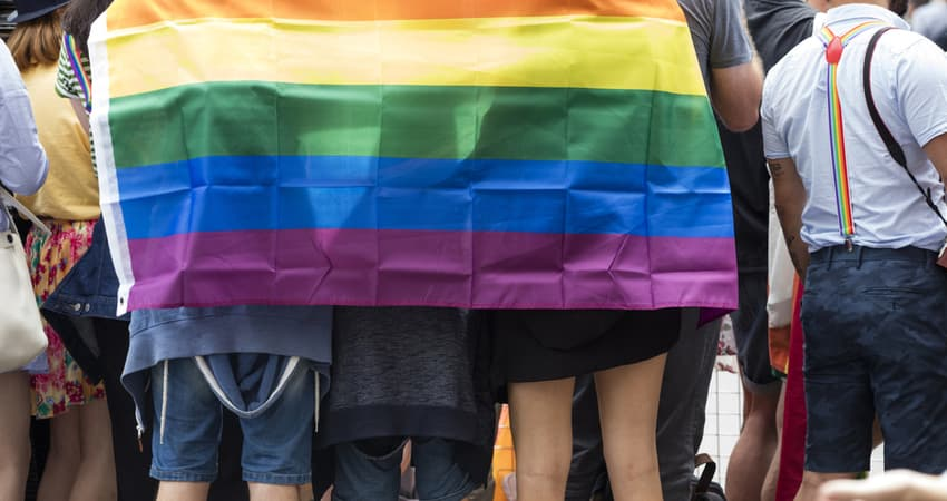 a group standing together under a pride flag