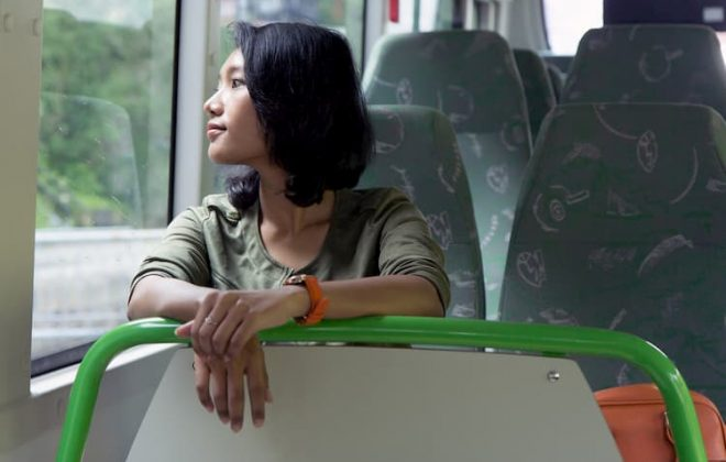 Woman looking out window on bus