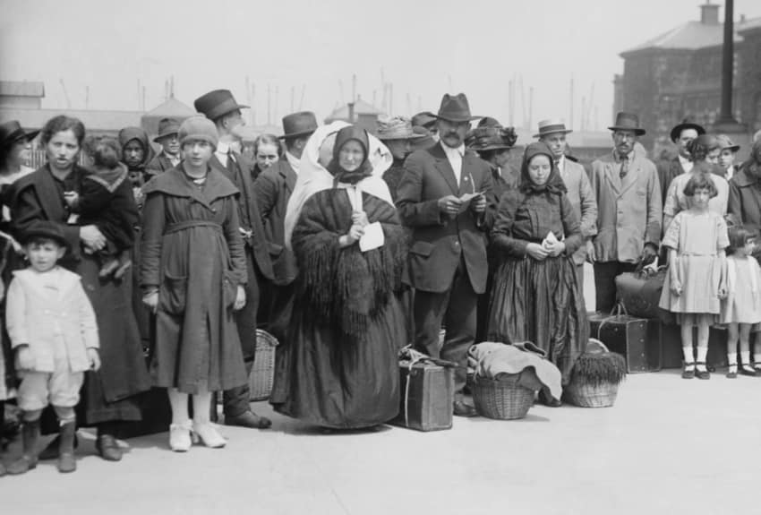 A black and white photograph of the immigrants arriving at Ellis Island
