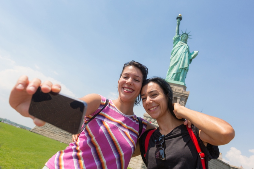 Two girls take a selfie with the Statue of Liberty
