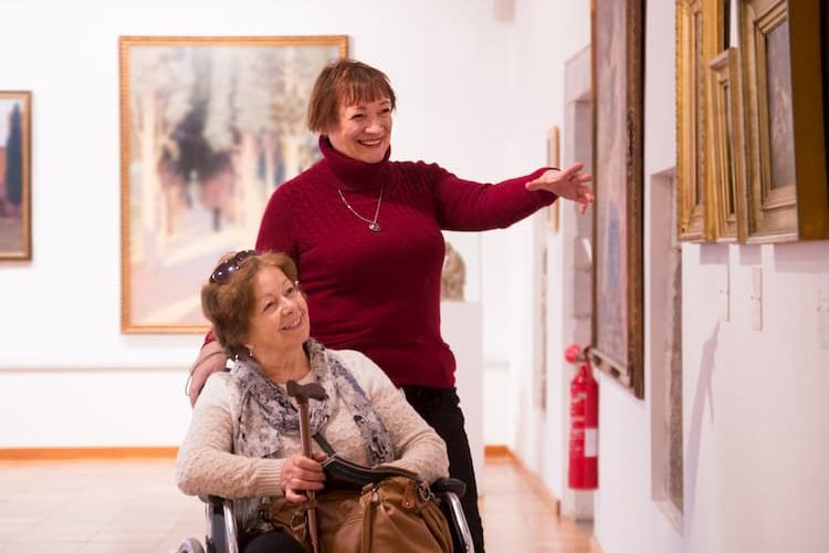 Two women at art museum, one using wheelchair and one walking