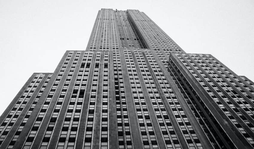 A black and white photograph of the Empire State Building, viewed from ground level looking up