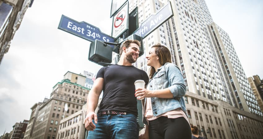 A young man and woman stand under the streets signs at the intersection of E 34th Street and 5th Avenue in New York City