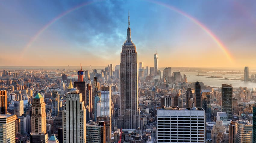 The Empire State Building from a distance, the surrounding city and a rainbow visible in the background