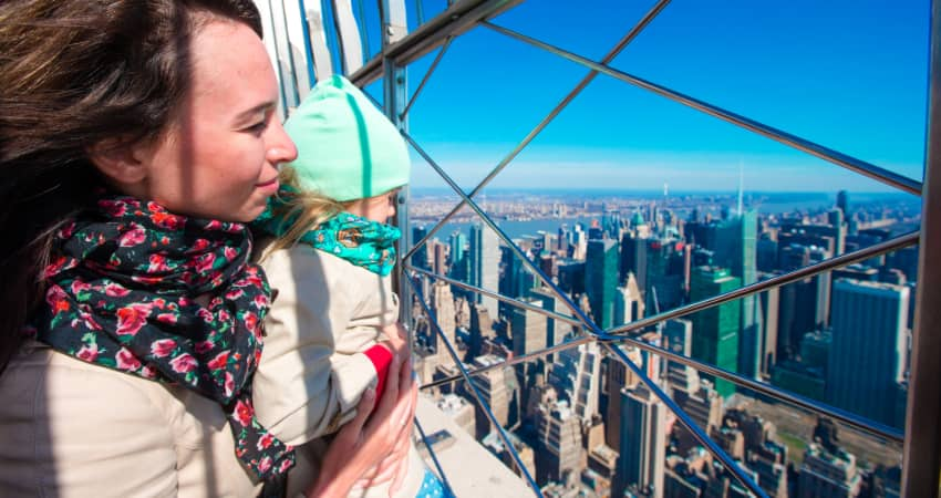 A mother and child stand at the top of the Empire State Building and take in the view