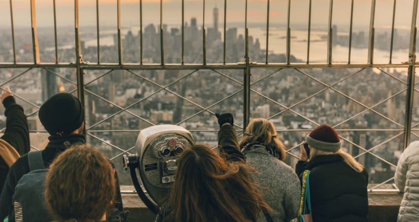 A crowd of tourists stand at the top of the Empire State Building, looking out across the Manhattan skyline