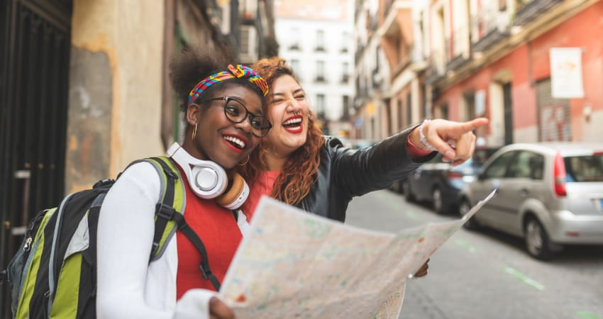 Two women with a map walk the streets on New York City