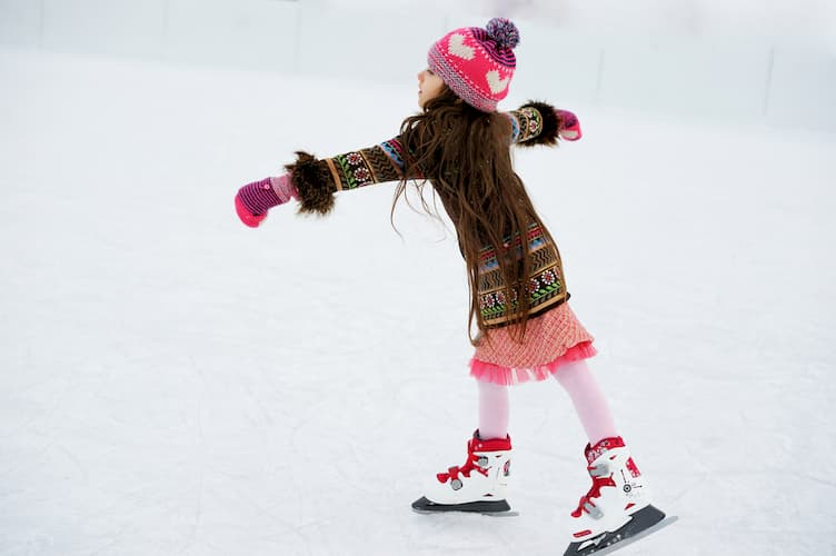 Little girl ice skating in winter clothes