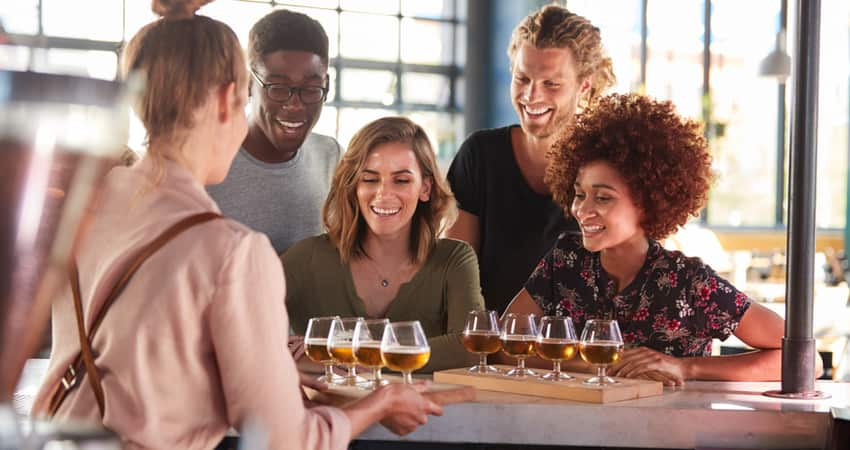 A group of friends at a brewery being served flights