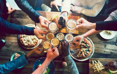A large group of friends toast their glasses of beers