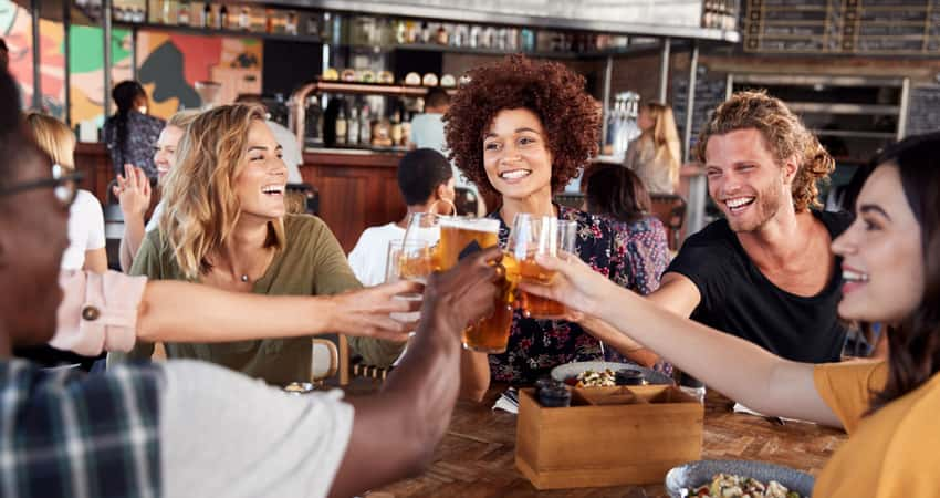 A group of friends toasting beer at a bar table