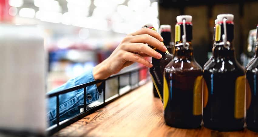 Close up of a hand grabbing beer at a store
