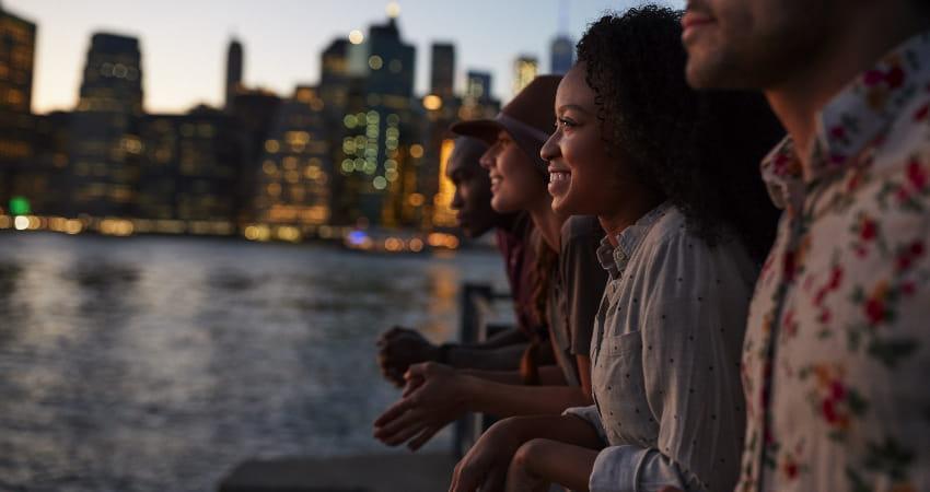 A group of friends watch the sun set in Manhattan