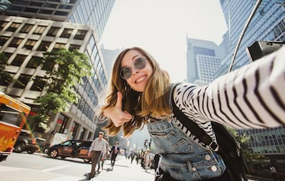A woman in sunglasses takes a selfie in a busy NYC street