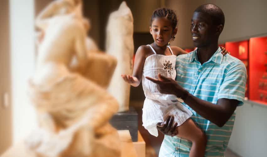 A father and child looking at sculptures in a museum