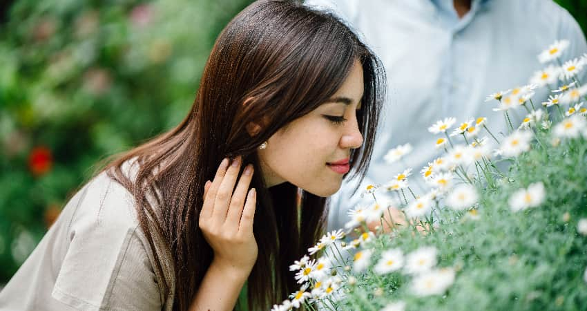 A woman smiles and smells flowers in a botanical garden