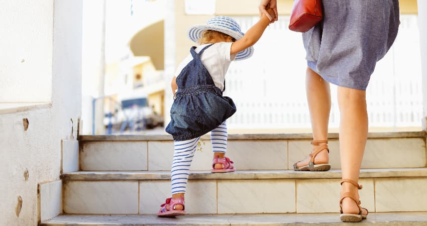 A parent and toddler climb a set of outdoor stairs in a city