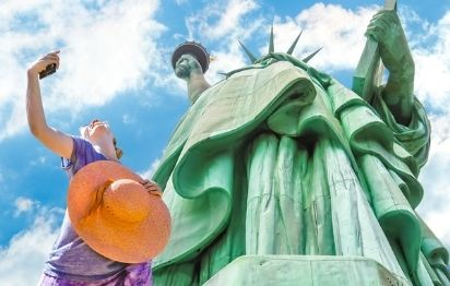 Woman taking selfie in front of the Statue of Liberty