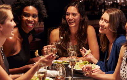 friends gather around a table of food and smile at one another