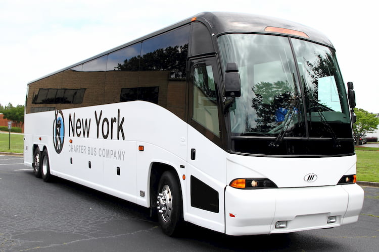 a bus from new york charter bus company sits in a parking lot before a trip