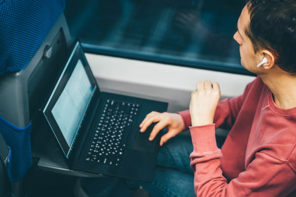 a man sits on a shuttle bus with his laptop